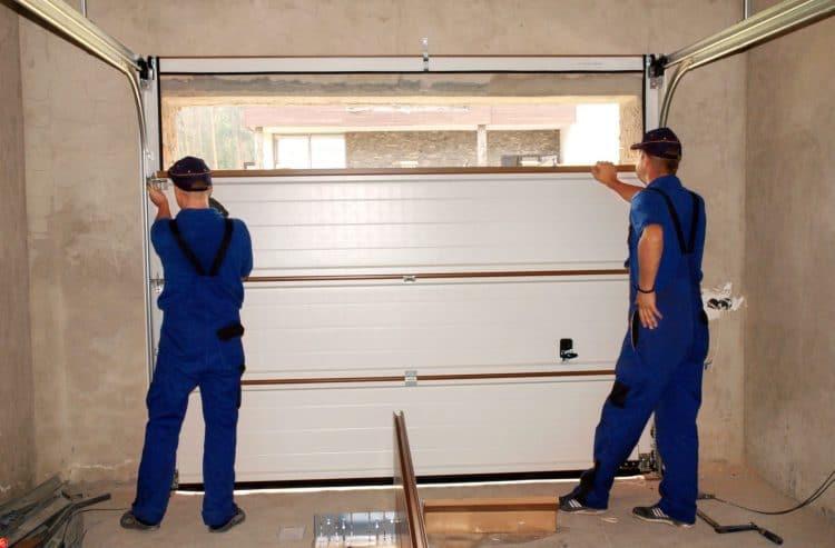 contractors repairing a damaged garage door
